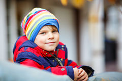 Happy cute little kid boy on autumn day in colorful clothes Stock Images