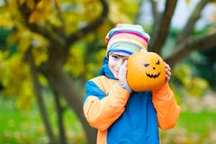 Happy cute little kid boy with halloween pumpkin lantern on autu. Happy cute little kid boy with halloween pumpkin lantern. Funny child in colorful clothes Royalty Free Stock Photography