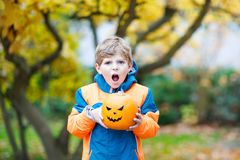 Happy cute little kid boy with halloween pumpkin lantern on autumn. Happy cute little kid boy with angry face and halloween pumpkin lantern. Funny child in Royalty Free Stock Photos