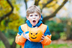 Happy cute little kid boy with halloween pumpkin lantern on autumn. Happy cute little kid boy with angry face and halloween pumpkin lantern. Funny child in Royalty Free Stock Image