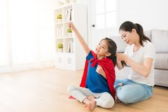 Happy cute little kid daughter wearing red cloak. Play as superhero and making ready to fly posing sitting on living room wooden floor when her mother helping royalty free stock images