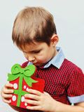Happy cute little kid holding red gift box isolated over the white background Royalty Free Stock Photo