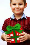 Happy cute little kid holding red gift box isolated over the white background Stock Image