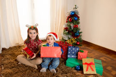 Happy Cute little kid Santa Claus hat and his beautiful sister Stock Photography