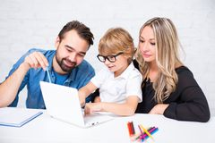 Happy cute little school boy in glasses doing homework with pare Royalty Free Stock Images