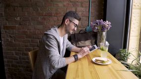 Happy cute male college student using tablet computer. guy sitting in a cafe with a tablet in her hands stock footage
