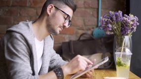 Happy cute male college student using tablet computer. guy sitting in a cafe with a tablet in her hands stock video footage