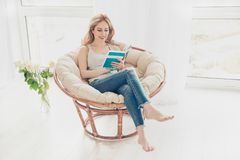 Happy cute pretty woman reading book in the armchair on the week stock image