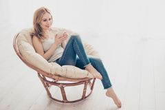 Happy cute pretty woman sitting in the armchair on the weekend w royalty free stock photo