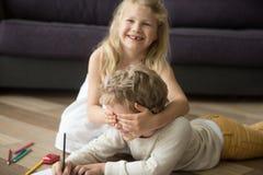 Happy cute siblings enjoying playing together, sister closing br Stock Photos