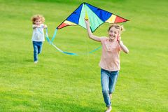 Happy cute siblings playing with kite while running on green lawn. In park royalty free stock image