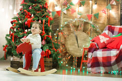 Happy cute small boy riding wooden rocking horse in front of christmas tree and presents on Christmas time or New Year Royalty Free Stock Images