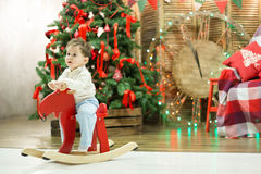 Happy cute small boy riding wooden rocking horse in front of christmas tree and presents on Christmas time or New Year Stock Photography