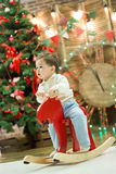Happy cute small boy riding wooden rocking horse in front of christmas tree and presents on Christmas time or New Year Royalty Free Stock Photos