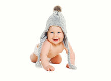 Happy cute smiling baby in knitted grey hat crawls on white Stock Photography