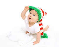 Happy cute smiling baby in knitted hat crawls on white Royalty Free Stock Photography