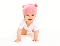 Happy cute smiling baby in knitted pink hat crawls on white Royalty Free Stock Image