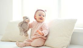 Happy cute smiling baby with teddy bear toy home in white room Royalty Free Stock Photo