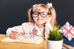 Studying in Classroom. Happy cute smiling girl wears in smart eyeglasses learning English language with book before dark background stock images