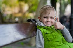 Happy smiling little blonde child show ok sign sitting on a bench Royalty Free Stock Images