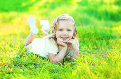 Happy cute smiling little girl child lying on grass Royalty Free Stock Photography