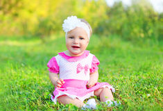 Happy cute smiling little girl child sitting on grass in summer Royalty Free Stock Image