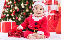 Happy cute smiling little santa claus baby with gifts and christ Royalty Free Stock Photos