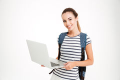 Happy cute student girl with backpack standing and holding laptop Stock Images