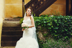 Happy cute stylish  bride is posing on the background old stairs Royalty Free Stock Photo