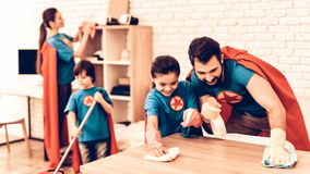 Happy Cute Super Heroes Family Cleaning Room. Father with Kids Washing the Table at Home. Cleaning Day Concept. Kids Helping House Chores. Parent Concept stock photos