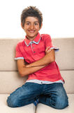 Happy cute teenager sitting on sofa Stock Photo