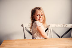 Happy cute toddler girl playing at home in kitchen. On wooden chair Royalty Free Stock Image