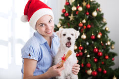 Happy cute woman holding bone gift for her pet dog, christmastim Royalty Free Stock Images
