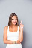 Happy cute woman pointing finger up Royalty Free Stock Image