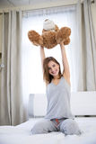Happy cute woman sitting on the bed Stock Photography
