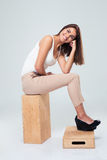Happy cute woman sitting on the wooden box Royalty Free Stock Photo