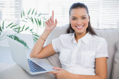 Happy cute woman using laptop sitting on cosy sofa Stock Photo