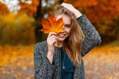 Happy cute young attractive woman with a smile in a fashionable coat is standing in the park and covering her face. With yellow autumn maple leaves. Funny royalty free stock photos