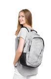 Happy and cute young blonde girl in casual clothes with a large gray backpack on his back, isolated on a white background. royalty free stock images