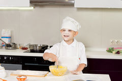 Happy cute young boy baking in the kitchen Royalty Free Stock Photo