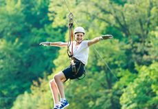 Happy, cute, young boy in white t shirt and helmet having fun and playing at adventure park, flying on the ropes. stock photos