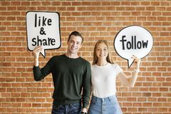 Happy cute young couple holding a thought bubble with social medHappy cute young couple holding a thought bubble with social media stock photos