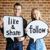 Happy cute young couple holding a thought bubble with social media concept words royalty free stock photo