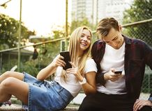 Happy cute young couple in the park using smartphones together royalty free stock photography