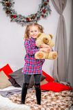 Happy cute young girl in a checkered blue-red dress standing on the bed with a teddy bear and hugging him against the background o stock photos