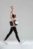 Happy cute young woman athlete walking and holding weighing scale Royalty Free Stock Image