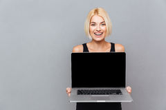 Happy cute young woman holding blank screen laptop Royalty Free Stock Images