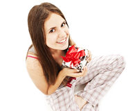 Happy cute young woman holding gift / present. Royalty Free Stock Photos