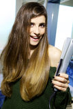 Happy cute young woman with iron ready to straighten long silky hair Stock Image
