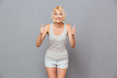 Happy cute young woman showing thumbs up with both hands Stock Photos